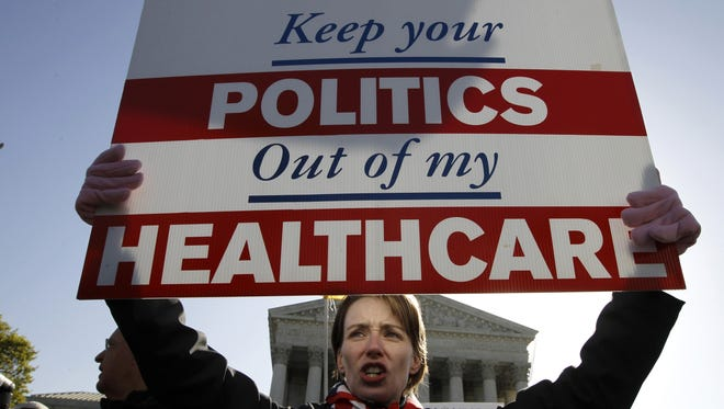 Amy Brighton from Medina, Ohio, who opposes health care reform, rallies in front of the Supreme Court  in Washington, Tuesday, March 27, 2012.