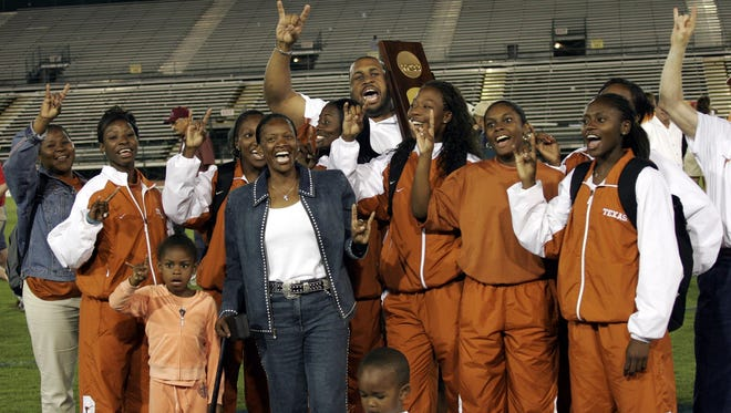 """Members of the Texas women's team give the """"hook 'em horns"""" sign after Texas won the women's team title at the NCAA track and field finals Saturday, June 11, 2005, in Sacramento. In front is coach Beverly Kearney, in jeans."""