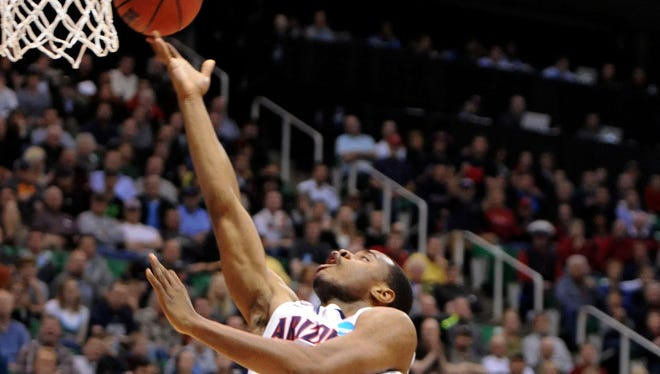 Arizona Wildcats guard/forward Kevin Parrom drives to the basket on Harvard Crimson guard Laurent Rivard in the first half during the third round of the NCAA basketball tournament at EnergySolutions Arena.
