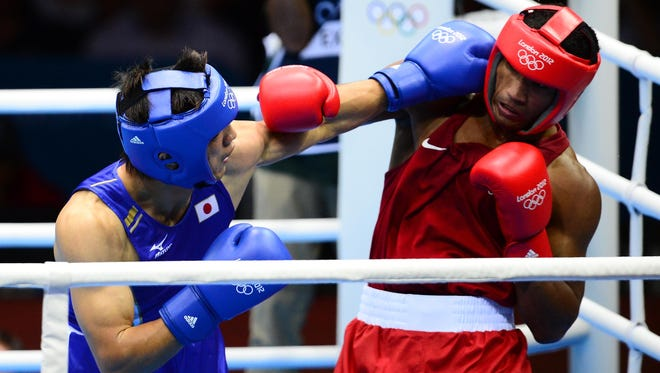 Ryota Murata of Japan, in blue, fights Esquiva Falcao Florentino of Brazil in the men's light fly 49k final bout during the London 2012 Olympic Games.