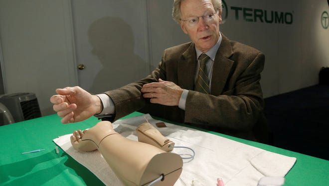 Dr. Spencer King, an Atlanta cardiologist,  demonstrates how doctors can open blocked heart arteries by going through an arm. He was using a model at the American College of Cardiology conference earlier this month in San Francisco.