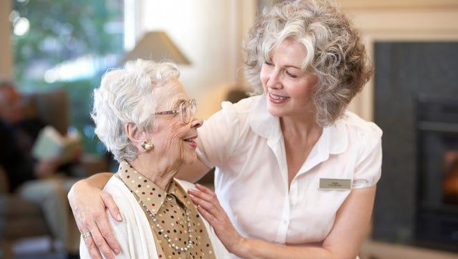 Nurse embracing senior woman in retirement home.