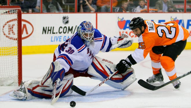 New York Rangers goalie Henrik Lundqvist swipes the puck away from Flyers center Max Talbot in the second period of a game that the Rangers won 5-2.