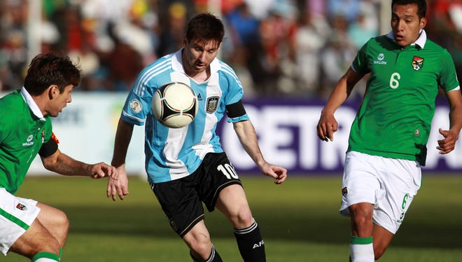 Argentina's Lionel Messi, center,  fights for the ball with Bolivia's Ronald Raldes, left, and Walter Veizaga during a World Cup 2014 qualifying soccer match in La Paz, Bolivia.