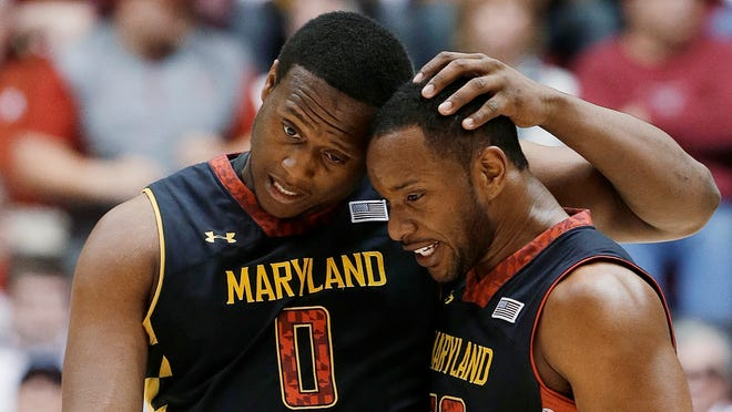 Maryland's Charles Mitchell and Dez Wells embrace near the end of Maryland's 58-57 win over Alabama during an NIT college basketball game in Tuscaloosa, Ala.