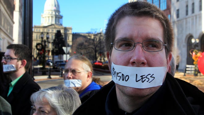 Protesters hold a  silent protest in Lansing, Mich., on Wednesday, Dec. 12, 2012, a day after thousands of protesters rallied on the grounds as lawmakers pushed final versions of right-to-work legislation.