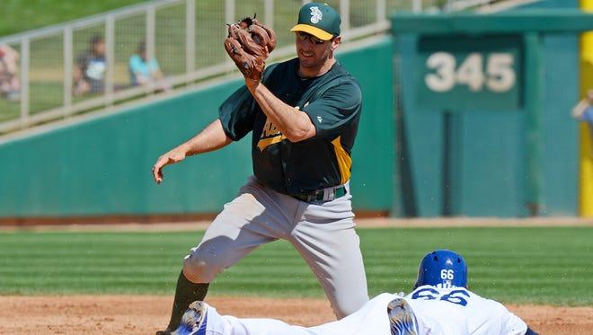 Oakland Athletics shortstop Adam Rosales tries to tag Los Angeles Dodgers center fielder Yasiel Puig at Camelback Ranch.