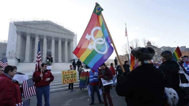 Marcos German-Dominguez waves a rainbow flag in front of the U.S. Supreme Court on March 26.