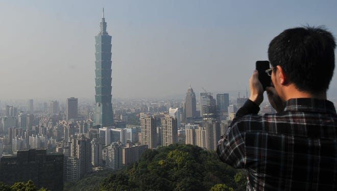 A tourist takes photos of the Taipei 101 tower in Taipei,Taiwan, on Feb. 25, 2013.