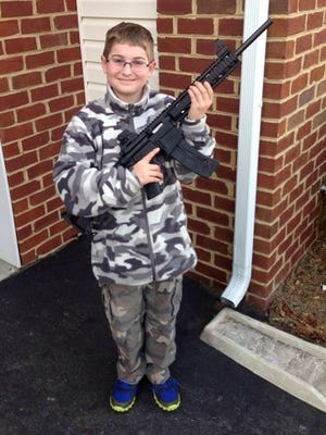 This undated photo provided by Shawn Moore shows his son, Josh, 10, holding a rifle his father gave him for his 11th birthday.