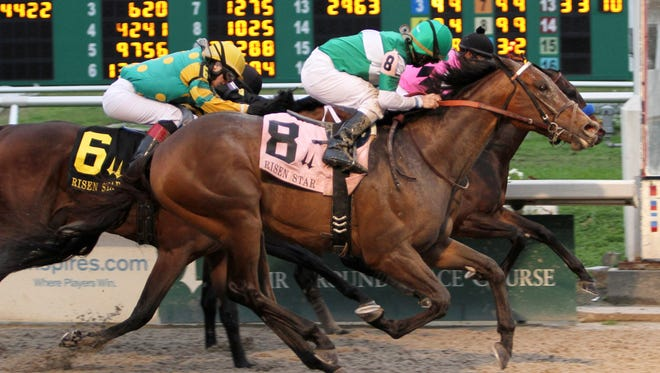 James Graham, aboard Ive Struck A Nerve, glances over at his competitors as his horse gets a nose in front of Code West, back right, and Palace Malace to win the Risen Star Stakes on Feb. 23rd.  Code West and Palace Malice are running in Saturday's Louisiana Derby.
