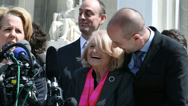 Edith Windsor, center, is embraced by Anthony D. Romero of the American Civil Liberties Union as her attorney, Roberta Kaplan, speaks Wednesday outside the U.S. Supreme Court.