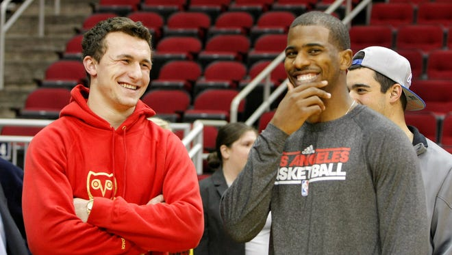 Texas A&M quarterback Johnny Manziel (left) talks to Los Angeles Clippers point guard Chris Paul (right) before a game against the Houston Rockets at the Toyota Center on Jan. 15. Manziel's interactions with pro athletes were some of the highlights of his Twitter feed, which he has put on hiatus since Sunday.