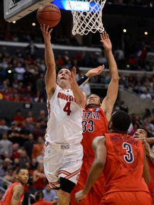 Ohio State Buckeyes guard Aaron Craft (4) shoots against Arizona Wildcats forward Grant Jerrett (33) and forward Kevin Parrom (3) during the second half of the semifinals of the West regional of the NCAA tournament.