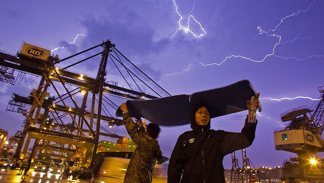 Striking dock workers cover themselves as lightning flashes across the sky during a sit-in at the Kwai Chung Container Terminal in Hong Kong. The workers are demanding higher wages, claiming they have not received a pay raise for 15 years.