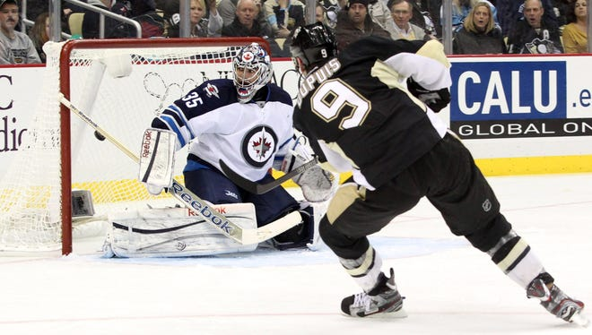 Pittsburgh Penguins right wing Pascal Dupuis shoots and scores past Winnipeg Jets goalie Al Montoya during the second period.