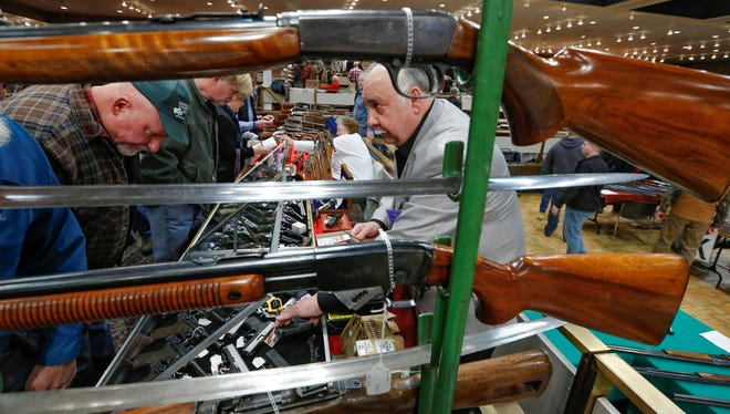 Gun store owner David Petronis of Mechanicville, N.Y., right, talks with a potential customer Jan. 26 at his table during the New York State Arms Collectors Association Albany Gun Show in Albany.
