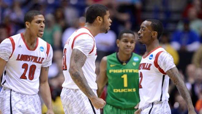 Louisville Cardinals players Wayne Blackshear (20), Chane Behanan (21) and Russ Smith (2) react in the first half during the semifinals of the Midwest regional of the tournament against the Oregon Ducks at Lucas Oil Stadium.