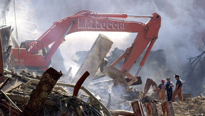 Firefighters and construction workers clear debris from the site of the Sept. 11, 2001, World Trade Center attacks on Oct. 4, 2001, in New York.