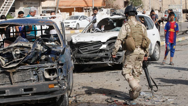 People and security forces gather at the scene of a car bomb attack in Qahira neighborhood of eastern Baghdad, Iraq, on Friday.