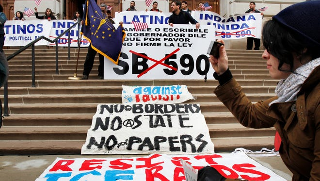 Irasema Rivera, an Indiana University student, takes a picture of a rally protesting Indiana's immigration legislation when it was being debated March 15, 2011, inside the Indiana Statehouse.