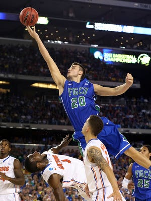 Florida Gulf Coast Eagles forward Chase Fieler (20) lays the ball up over the defense by Florida Gators center Patric Young (4) in the first half during the semifinals of the South regional of the NCAA tournament at Cowboys Stadium.