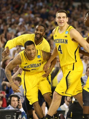 Michigan Wolverines guard Trey Burke (3) celebrates the overtime victory over the Kansas Jayhawks during the semifinals of the South regional of the NCAA tournament at Cowboys Stadium.