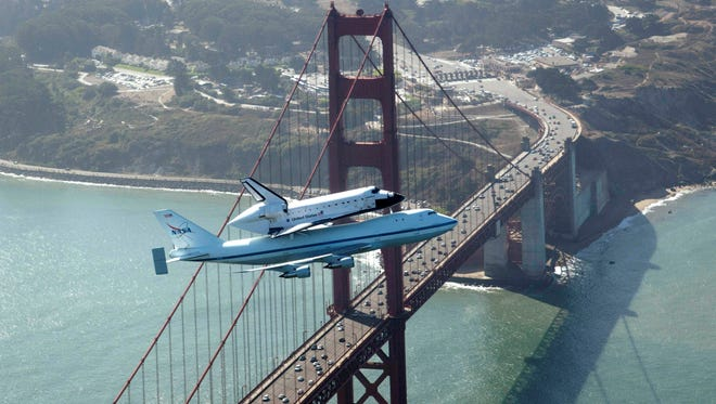 Space shuttle Endeavour and its 747 carrier aircraft soar over the Golden Gate Bridge in San Francisco during the final portion of its tour of California, Sept. 21, 2012.
