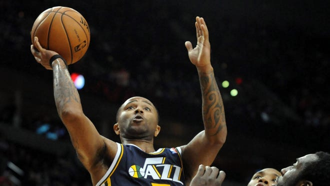 Utah Jazz point guard Mo Williams (5) drives to the basket on Portland Trail Blazers point guard Damian Lillard (0) and center J.J. Hickson (21) during the fourth quarter at the Rose Garden. The Jazz won the game 105-95.