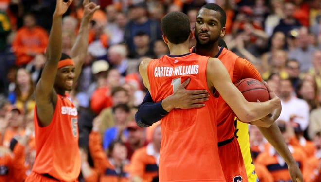 Syracuse's Michael Carter-Williams and forward James Southerland (back) celebrate in the final seconds of the 55-39 win over Marquette, clinching a berth in the Final Four.