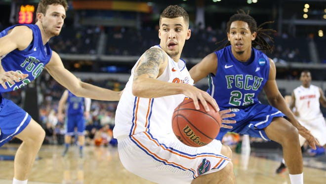 Florida guard Scottie Wilbekin (5) maneuvers around the defense of Florida Gulf Coast Eagles forward Eddie Murray (23) and guard Sherwood Brown (25) during the second half of the South Region semifinal Friday. The defensively strong Wilbekin's matchup with Michigan's guards is one to watch Sunday.