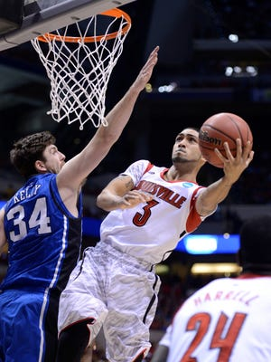 Louisville Cardinals guard Peyton Siva (3) shoots against Duke Blue Devils forward Ryan Kelly (34) in the first half during the finals of the Midwest regional of the 2013 NCAA tournament at Lucas Oil Stadium.