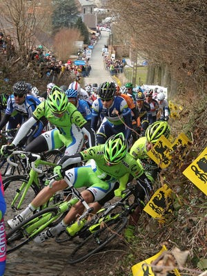 Cannondale Pro Cycling riders, right, fall as the pack climbs the steepest part of the Koppenberg hill, during the Tour of Flanders, in Melden, Belgium, Sunday.
