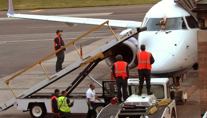 In this April 24, 2012, file photo, emergency responders and aircraft mechanics survey the damage to a JetBlue plane that made an emergency landing at the Westchester County Airport in Purchase, N.Y., after a bird strike.
