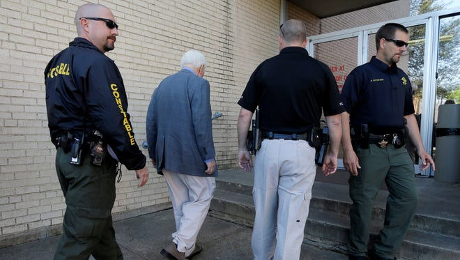 Kaufman County law enforcement officials escort an employee inside the county courthouse Monday, two days after the shooting deaths of the district attorney  and his wife at their home.