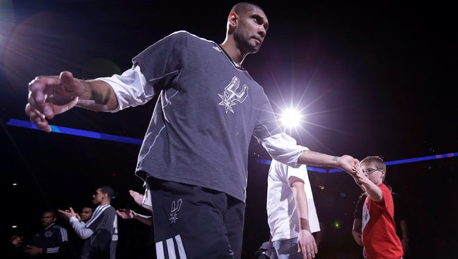 San Antonio Spurs' Tim Duncan shakes hands with fans as he is introduced prior to an NBA basketball game.