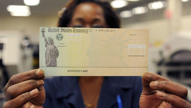 Treasury employee Linda Tarkenton of Philadelphia, Pennsylvania holds a blank U.S. Treasury check before it's run through a printer at the U.S. Treasury printing facility.