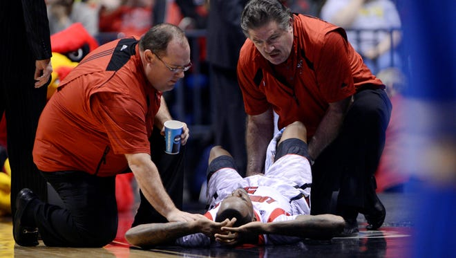 Louisville Cardinals guard Kevin Ware is treated by medical personnel after suffering a leg injury during the finals of the Midwest regional against the Duke Blue Devils at Lucas Oil Stadium.