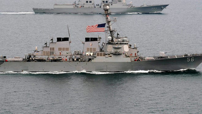 The Arleigh Burke-class guided-missile destroyer USS John S. McCain moves into formation in the waters off the Korean Peninsula during an exercise March 17.