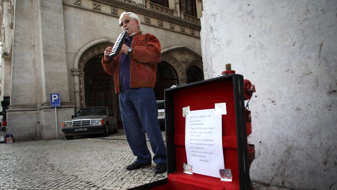 Jose Fonseca, 62, who has been unemployed for six months, plays music on the street for money in Lisbon, in this file photo.