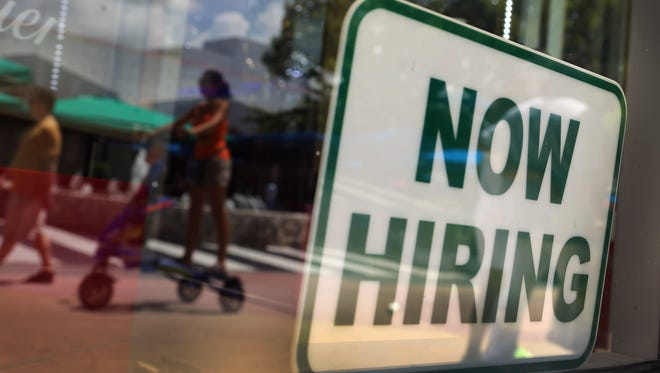 A ''Now Hiring'' sign is seen in a storefront window in Miami Beach on July 5, 2012.