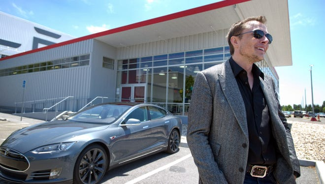 Elon Musk, CEO of Tesla Motors, with his Model S electric sedan at the factory in Fremont, Calif.