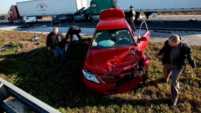 In this Jan. 29, 2012, photo, officials work at the scene of a multi-vehicle wreck on Interstate 75 at Paynes Prairie, south of Gainesville, Fla.