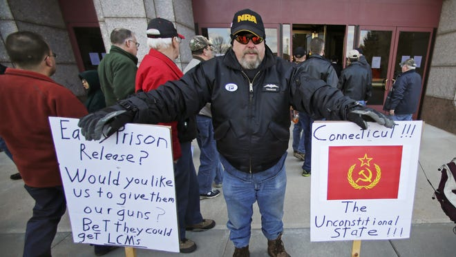 Paul Regish of East Hartford, Conn., holds signs as gun rights advocates enter the legislative office building at the Capitol in Hartford, Conn., Wednesday, where lawmakers were voting on tough new gun laws.