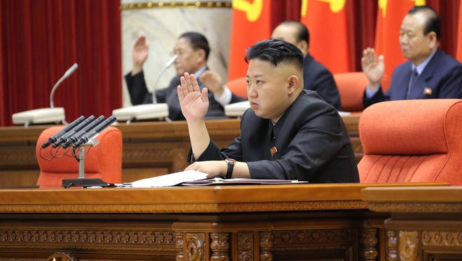 North Korean leader Kim Jong Un raises his hand with other officials to adopt a statement during a plenary meeting of the central committee of the ruling Workers' Party in Pyongyang, North Korea, on March 31.