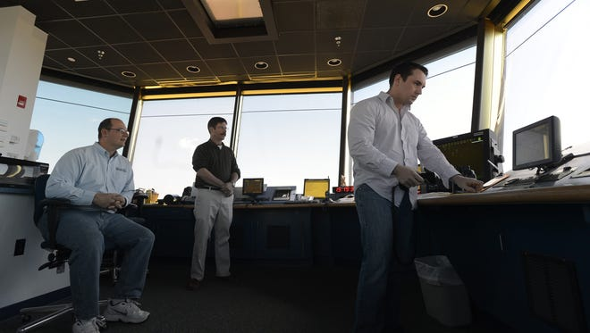 Air traffic controller, Abraham O'Keeffe, right, tracks an incoming flight during his shift at the Easton, Md., airport as tower manager, Micah Risher, left, and controller Johns Stevens watch.