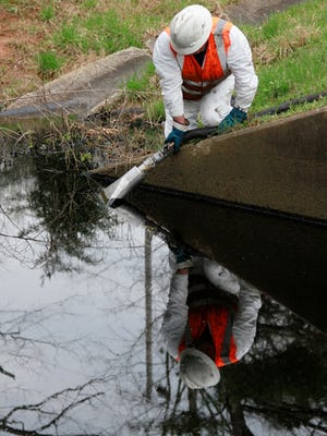 A worker starts to clean up oil that threatened Lake Conway after an ExxonMobile crude oil pipeline ruptured March 29 in Mayflower, Ark.