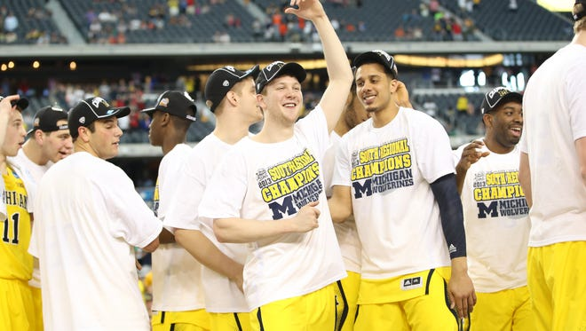 Michigan Wolverines guard Matt Vogrich, middle, celebrates with teammates as they defeat the Florida Gators 79-59 at Cowboys Stadium to advance to the Final Four.