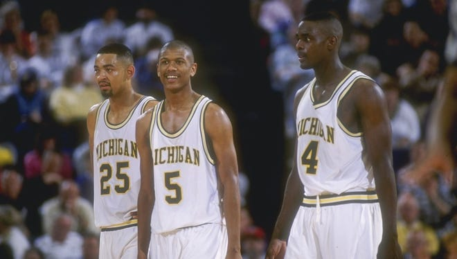 Michigan Wolverines forward Juwan Howard, left, guard Jalen Rose, center, and forward Chris Webber look on during a game against the Indiana Pacers.