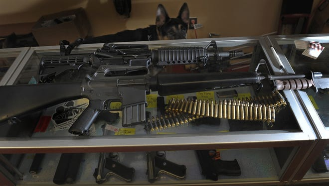 An SP1 M16 rifle with bayonet lays on the counter at Guns for America at the Nashville shop last month as guard dog Jet Ranger wanders the store.